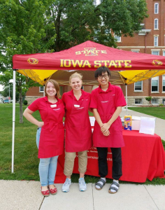 Three interns stand outside of an ISU tent at a farmers market