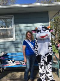Shana in her crown with a friend in a cow suit