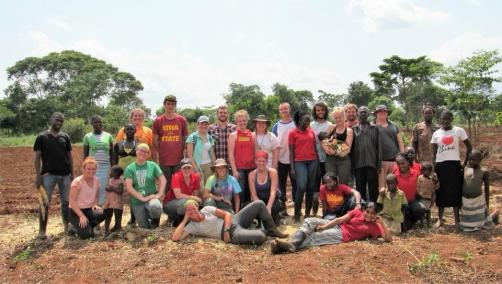 The spring break and semester students pose after planting a field of grain amaranthe at a NEC
