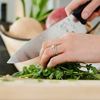 Woman chopping herbs with knife